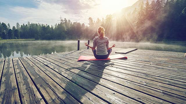 Woman meditating on a lake dock.