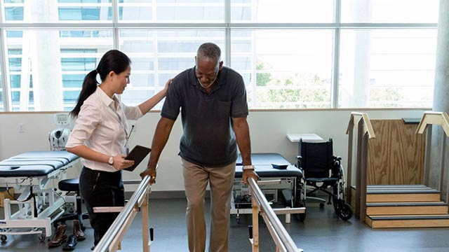 Man using parallel bars in physical therapy session