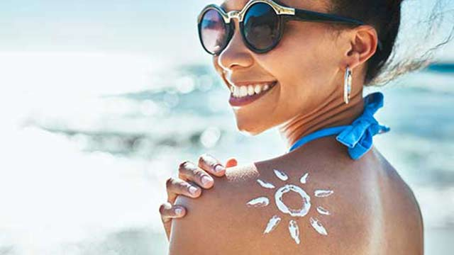 Woman with sunscreen on her shoulder