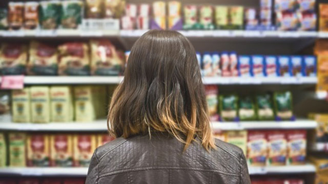 Woman staring at grocery store shelves