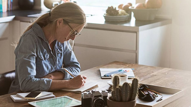 Woman sitting at her kitchen table, drawing in a notebook.