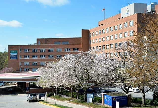 shot of Suburban Hospital with blossoming trees in front of the building entrance