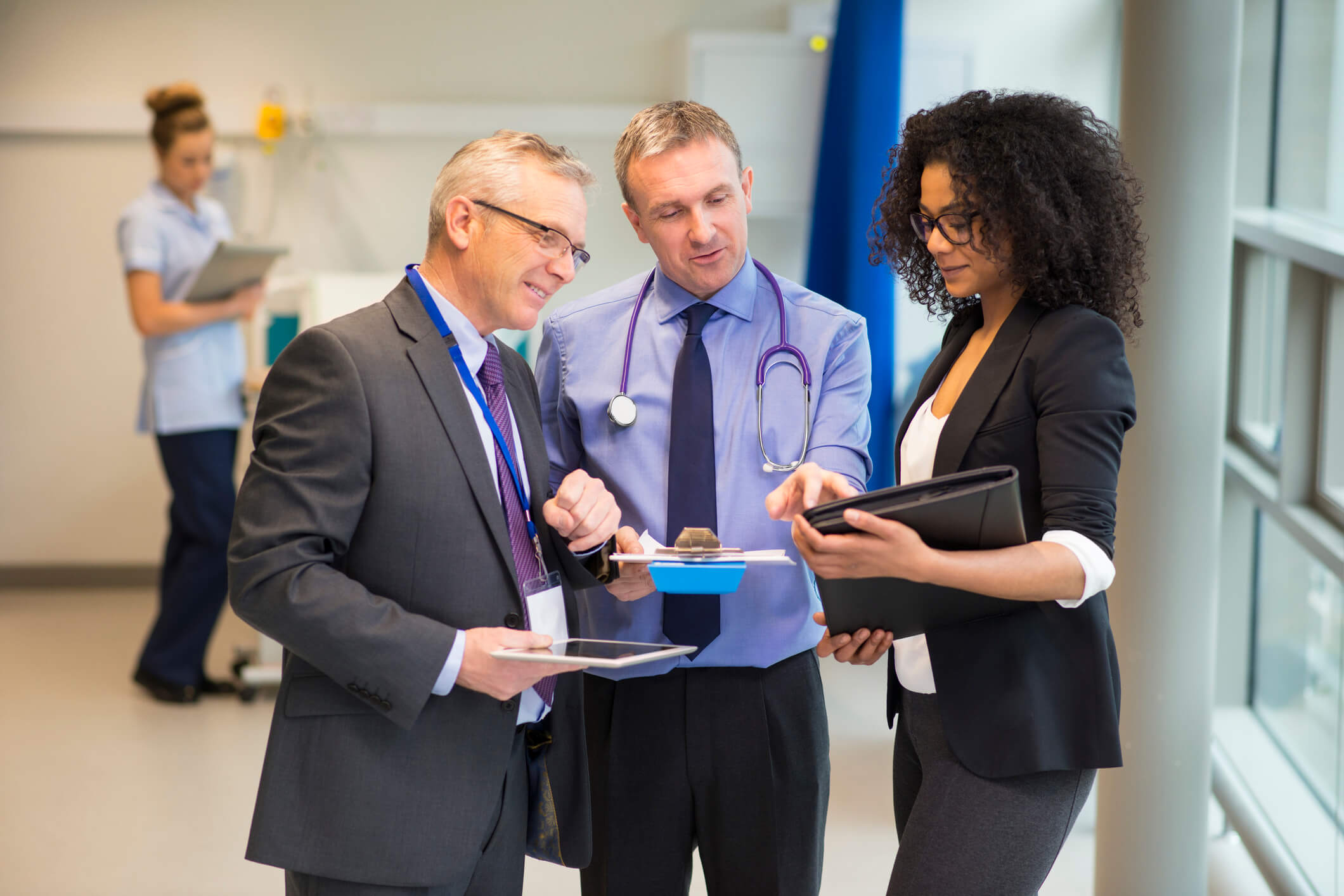 a doctor reviewing paperwork with two people in suits
