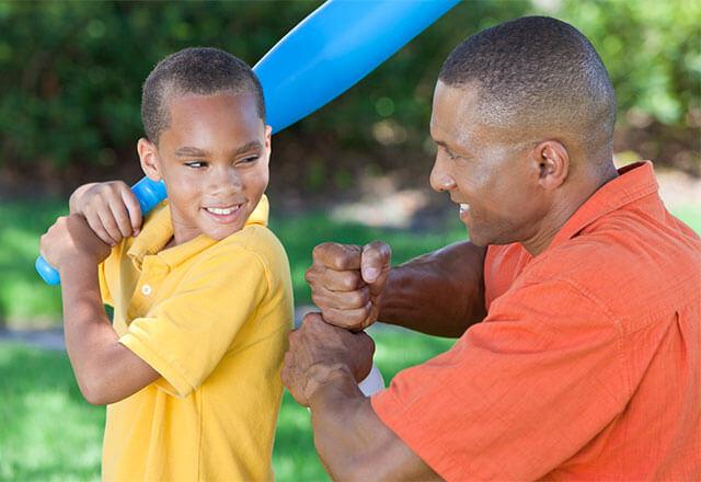 man playing baseball with his son