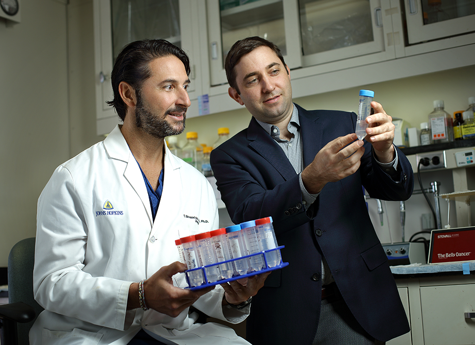 Two physicians looking at test tube