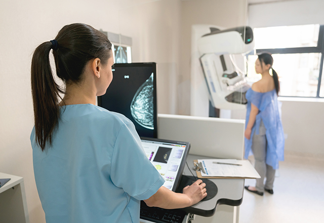 breast care - specialist performing mammogram