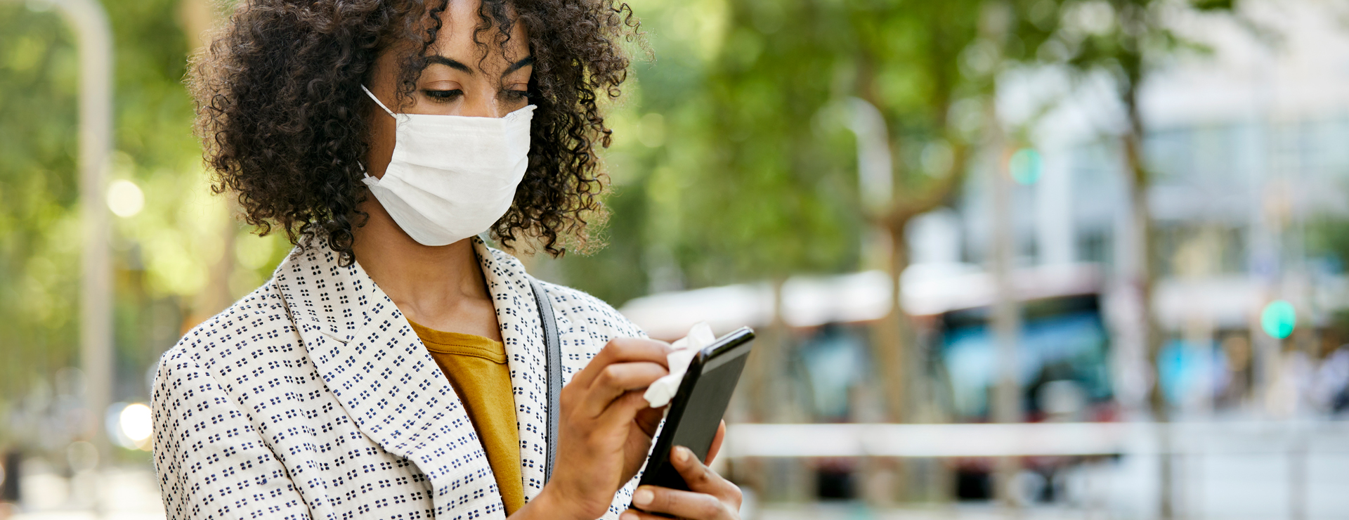 woman on her phone while wearing a face mask