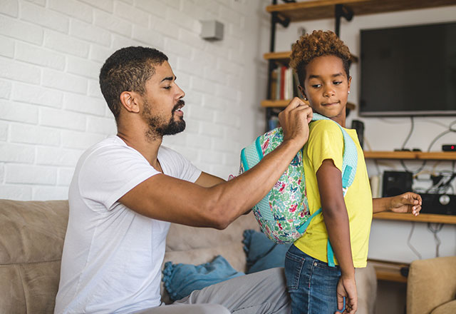 a father helps his daughter put on her backpack at home before school