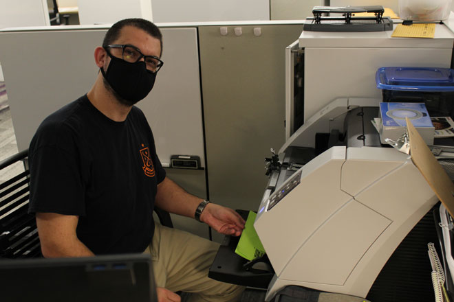A Johns Hopkins HealthCare employee working at his desk during the COVID-19 pandemic