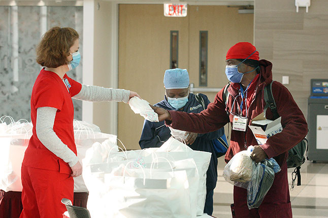 A suburban employee hands out lunch to clinical staff