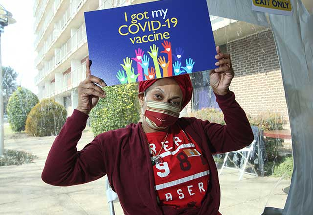 Community member holding a sign stating I got my COVID-19 vaccine.