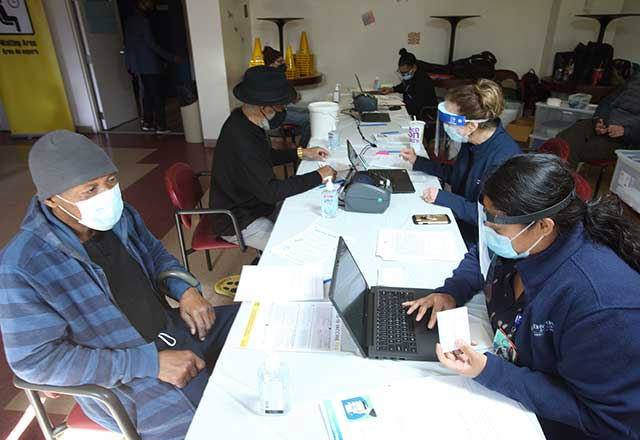 Community member being registered on a laptop by a clinic worker.