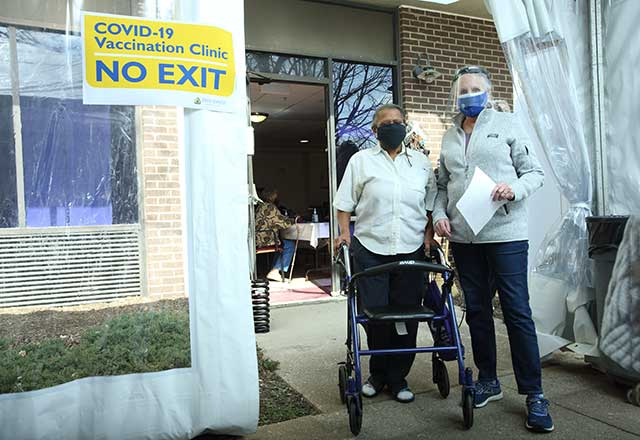 Healthcare provider escorting eligible community member to walk-in station.