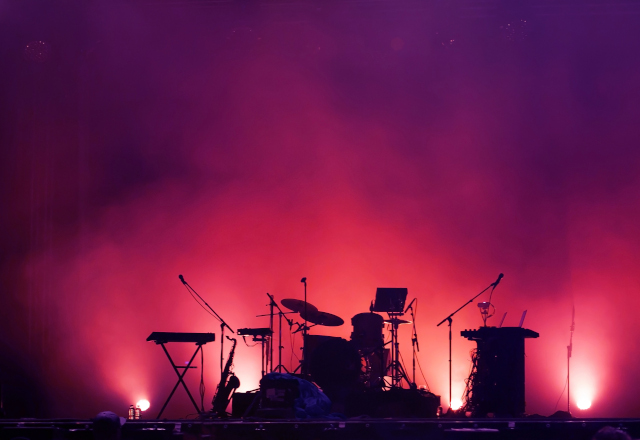 a drumset on stage backlit in pink light and fog