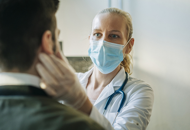 A doctor examines a patient's throat while wearing a mask.