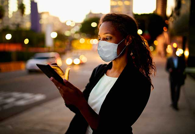 Woman with a mask checking her phone