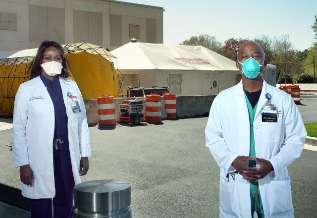 Two Black Hopkins doctors wearing masks stand outside in front of a testing site.