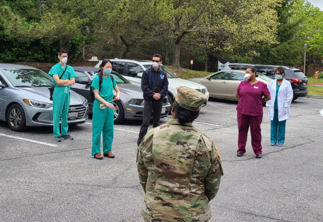 Members of the Go Team, facility staff and the National Guard meet in a parking lot
