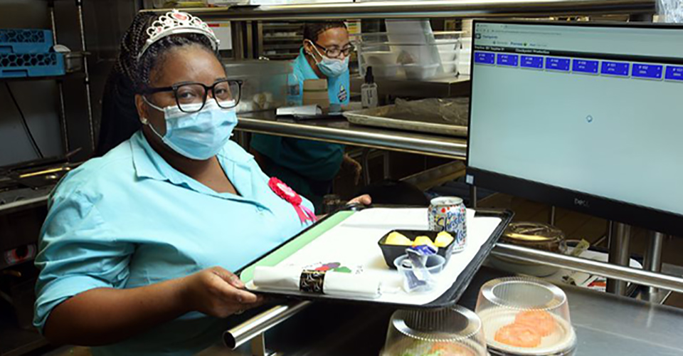 Dawn Silver wears birthday crown and PPE while holding tray of food