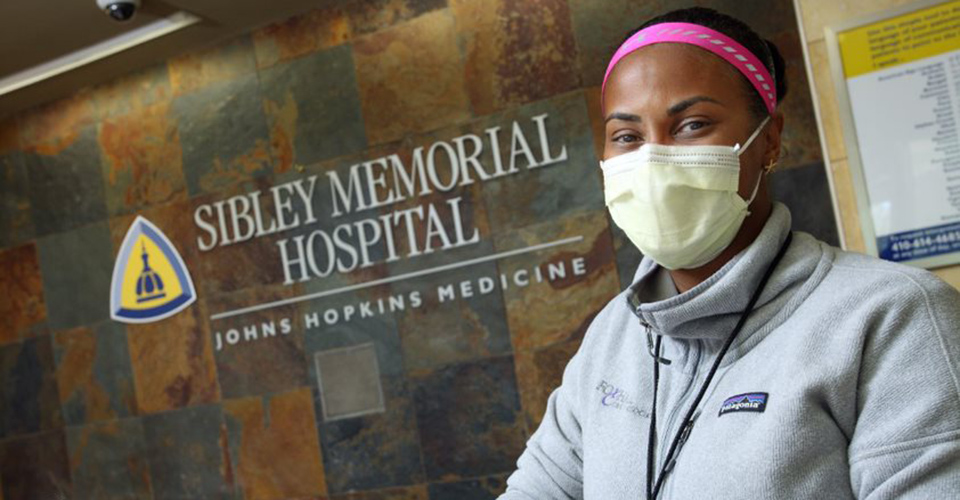 Lynne Lightfoote stands in front of Johns Hopkins Sibley Memorial Hospital