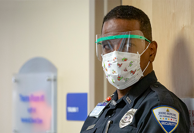 A security officer wears a mask
