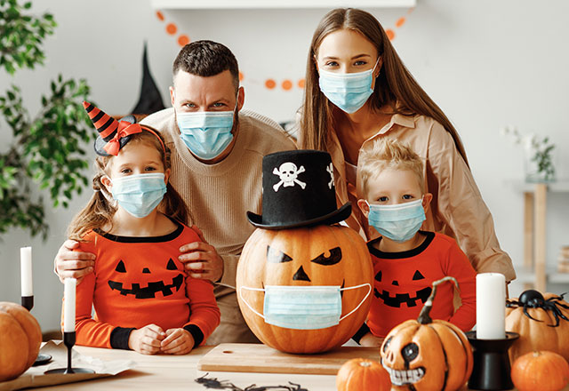 a family in Halloween attire poses together while wearing masks with a jack o' lantern also wearing a mask