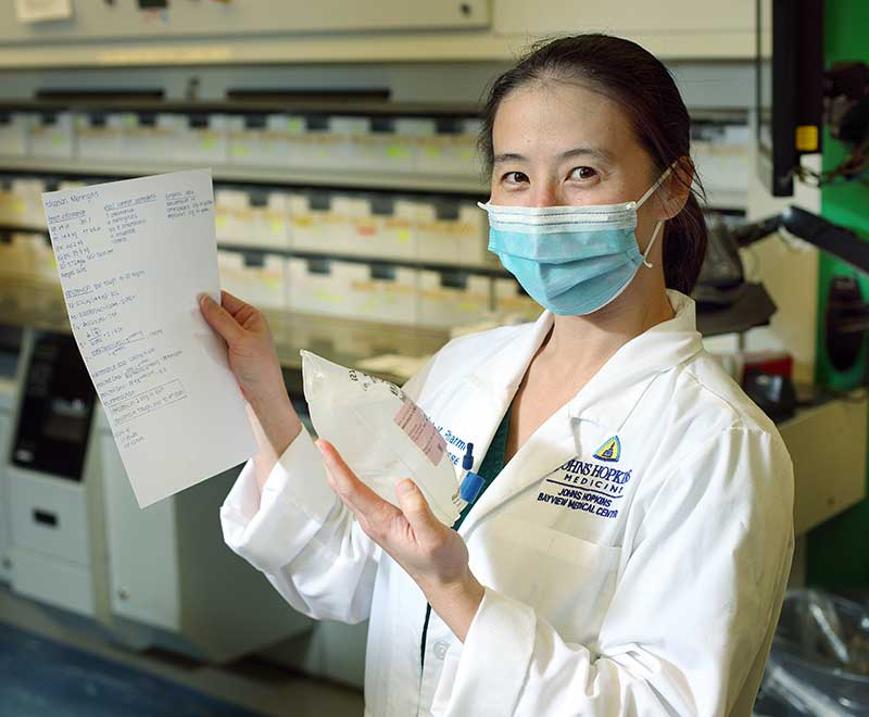 Pharmacy tech holding an IV pouch and a script