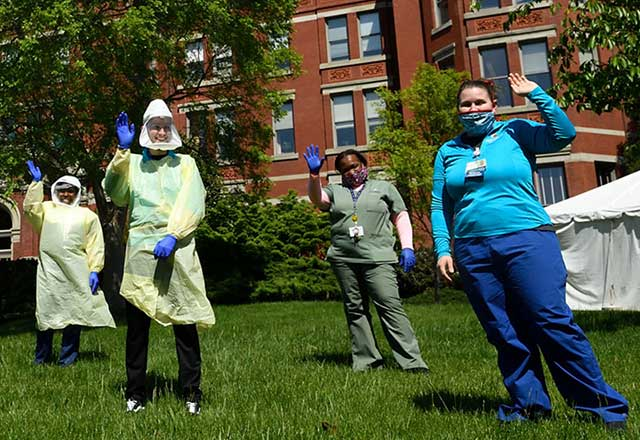 Hopkins staff wearing PPE wave together from the lawn in front of the Billings building.