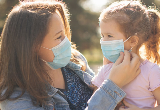 A mother and a child wear masks while outdoors.