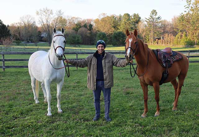 a former COVID-19 patient poses with his two horses
