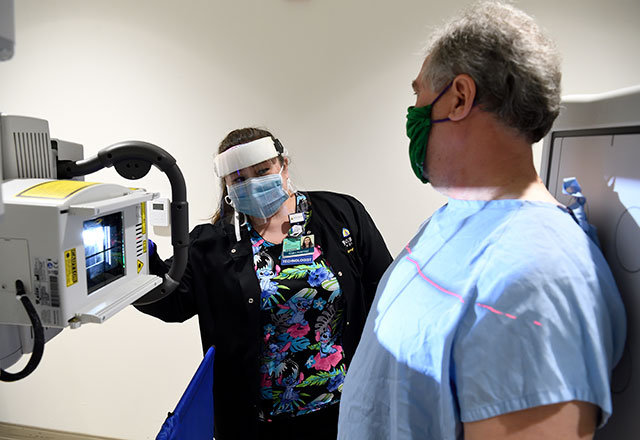 A patient and staff member wear PPE during an xray.