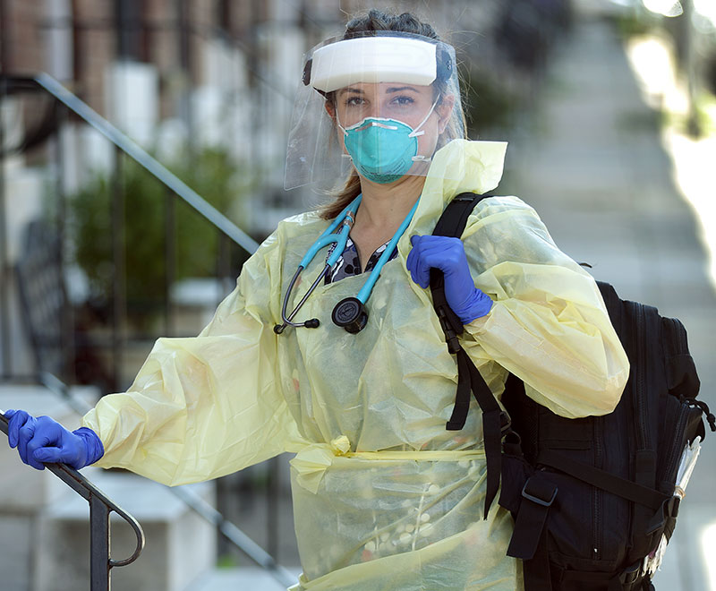 a home care nurse in PPE stands outside of a patient's house
