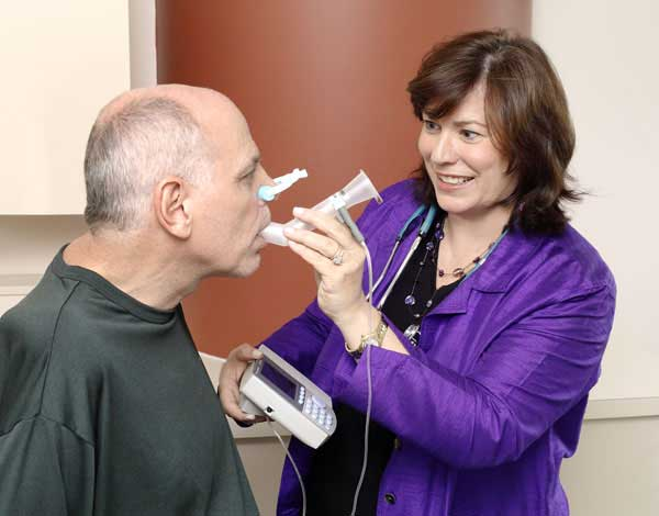 Lora Clawson helping a patient use a spirometer