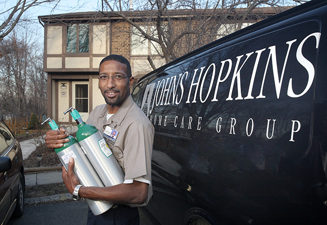 A Home Care employee stands holding oxygen tanks.