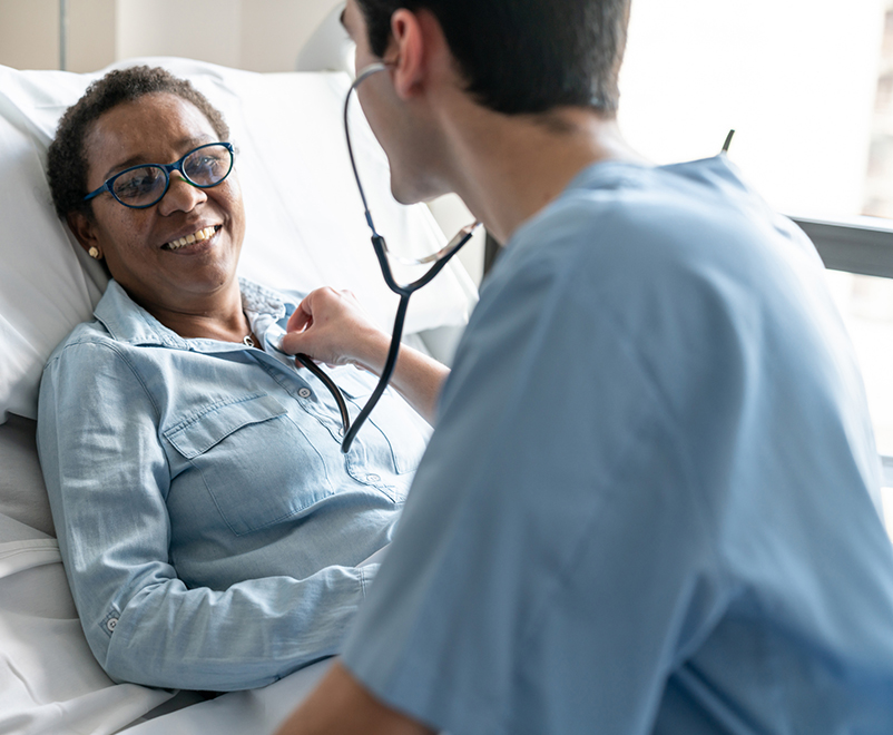 doctor listening to mature woman's chest