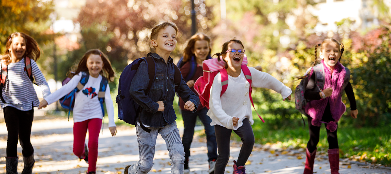 children running with backpacks on