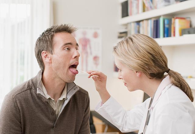 doctor examines patients throat