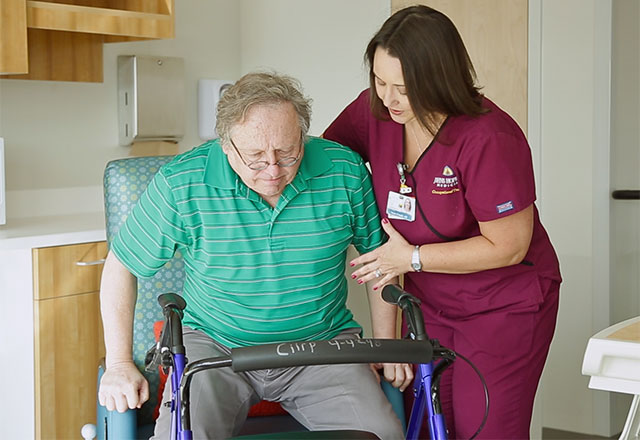 a therapist helps a patient stand up from a chair