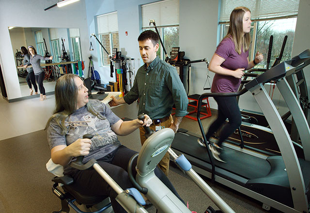 a therapist helps two women exercise