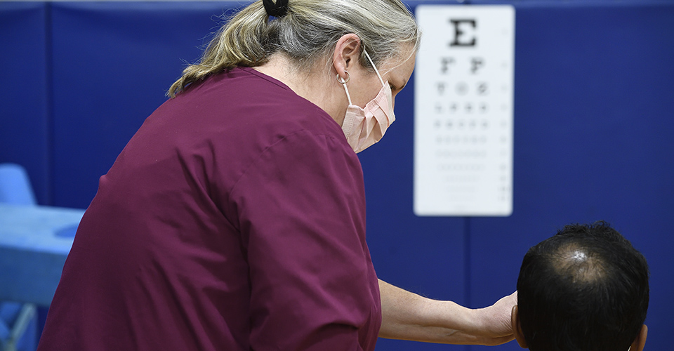 A health care worker conducts a vision test.