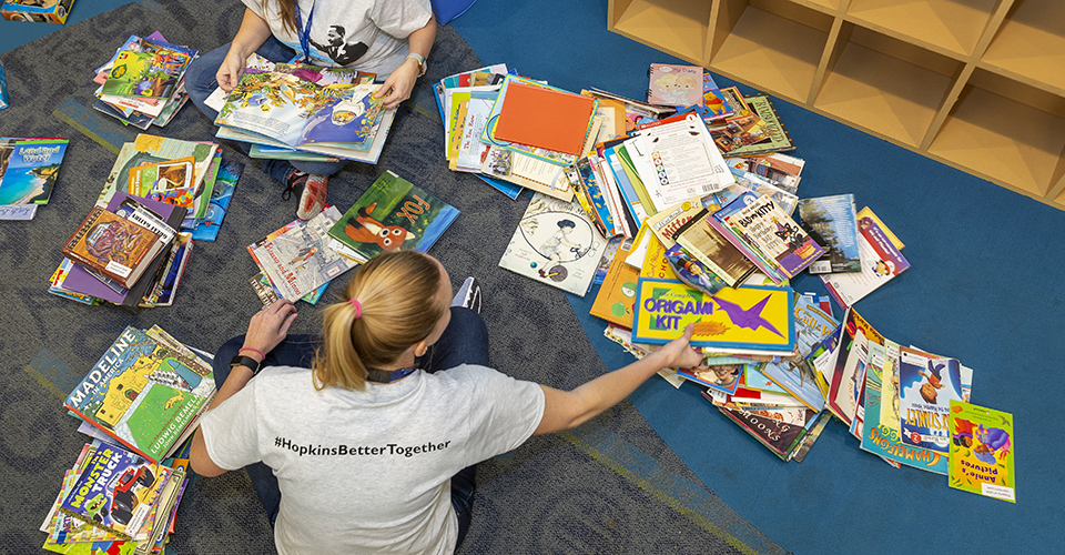 Volunteers sit on the floor, organizing children's books.