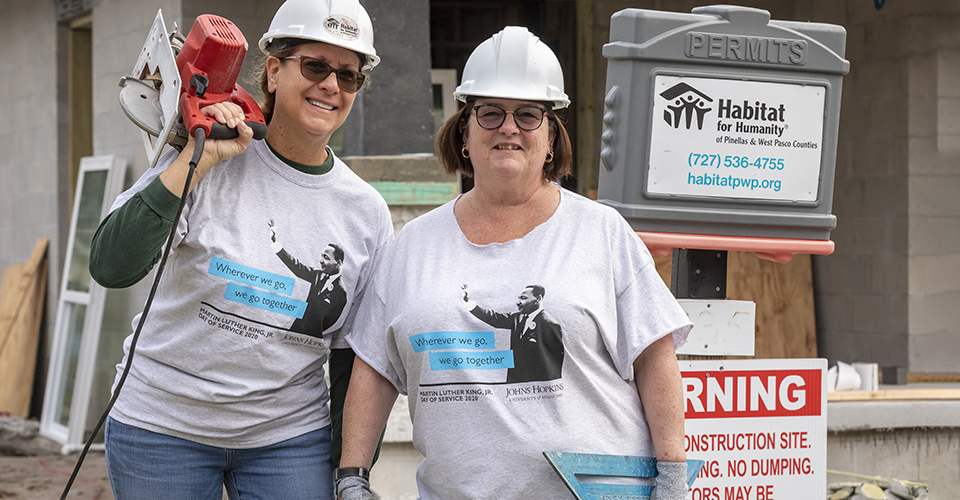 Two woman stand together outside of a construction site.
