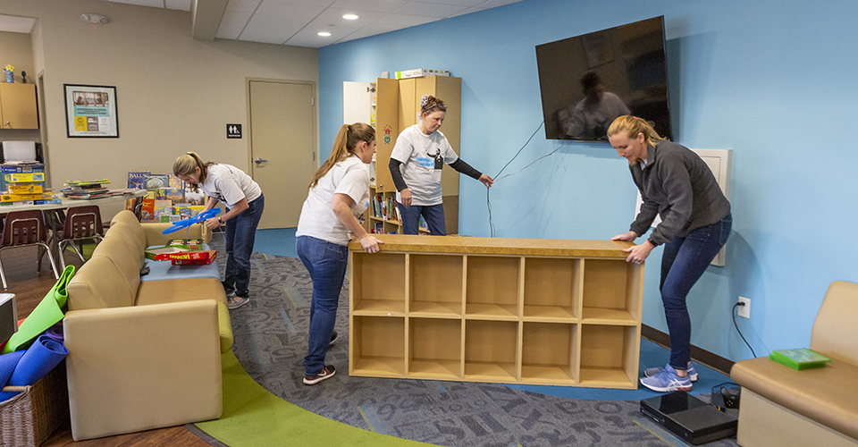 Volunteers move a bookshelf into place.