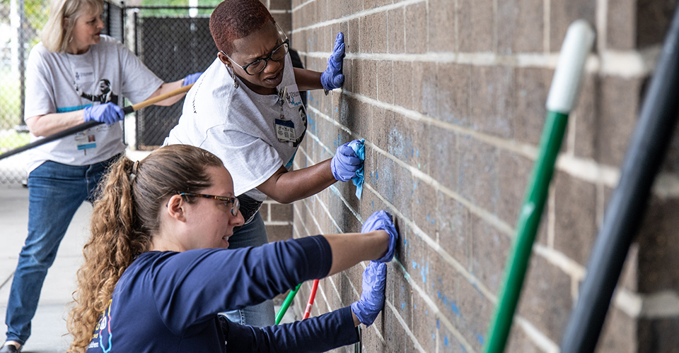 Volunteers clean the outside wall of a building.