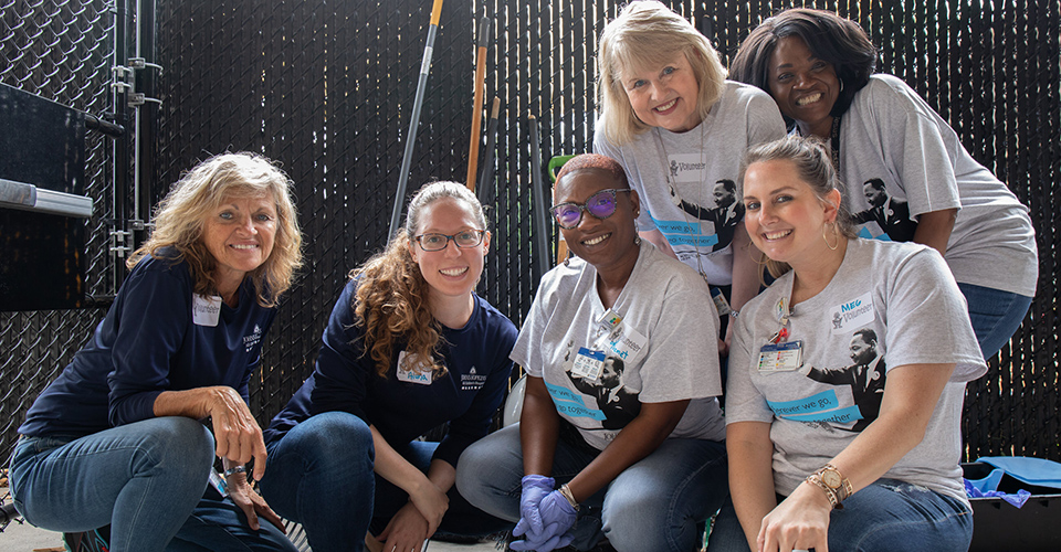A group of smiling volunteers pose together while working outside.