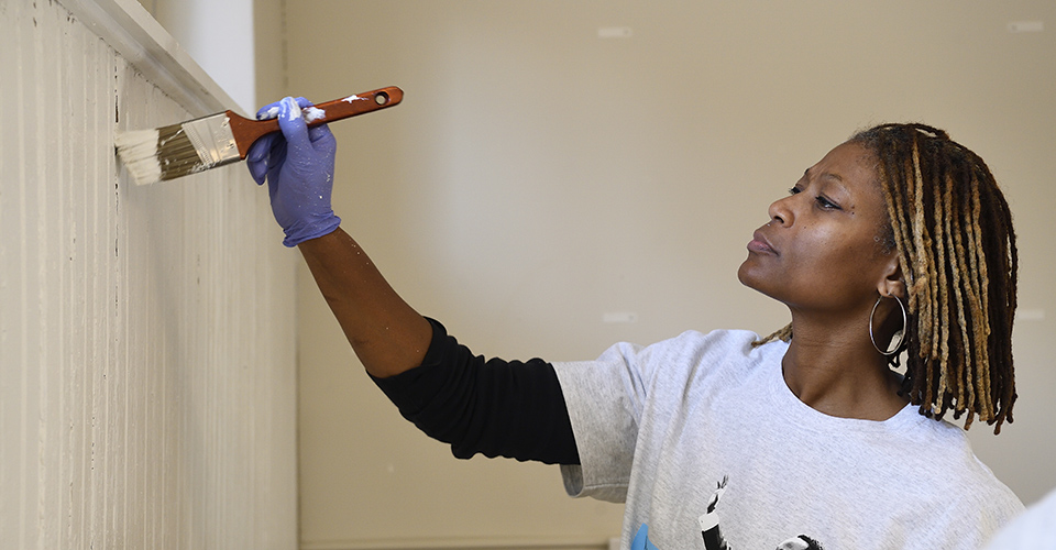 A woman painting a wall with a paintbrush.