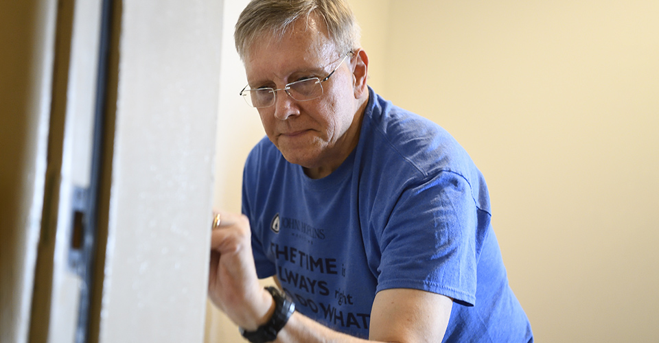 A man concentrates while painting a doorframe.