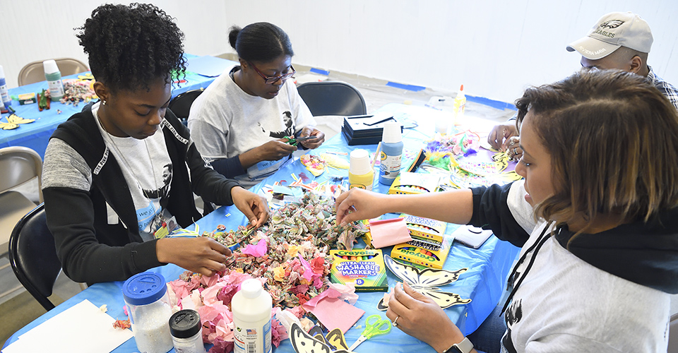 A group of people make crafts together.