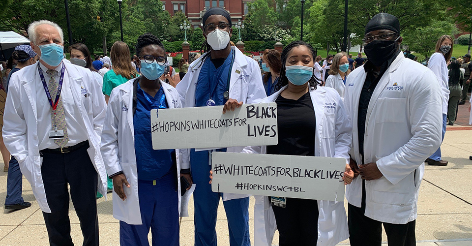 Hopkins staff standing in front of the Dome, holding signs in support of White Coats for Black Lives.