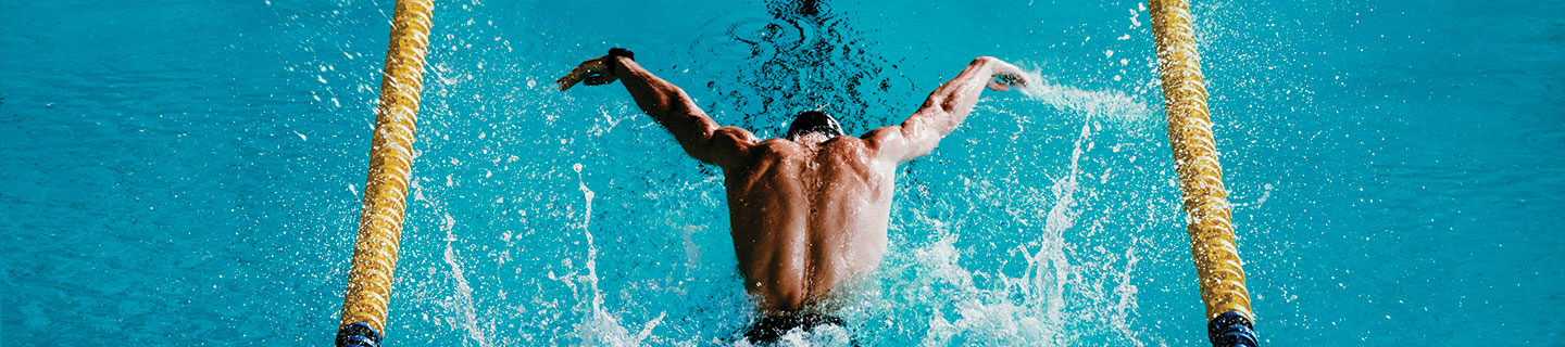 an overhead shot of a man swimming laps in a pool